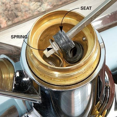 <b>Photo 4: Remove seats and springs</b></br> Remove both sets of seats and springs. When you reassemble the faucet using newer-style springs, guide the seats and springs into the hole with the narrow end of the spring facing up (see Figure A).