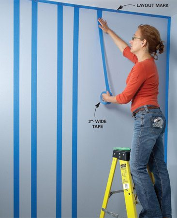 <b>Photo 1: Apply masking tape</b></br> Stripe the wall with masking tape. Stick the tape to the top of the wall, then stretch out a section long enough to reach the bottom before you press it to the wall.