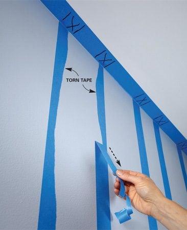 <b>Photo 2: Create a wavy edge</b></br> Tear one edge of each piece of tape to create a wavy edge. Wavy edges should face each other.