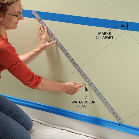 <b>Photo 1: Create the pattern</b></br> Draw a diamond pattern on the wall. First make marks 24 in. apart on the top and bottom pieces of masking tape. Then connect the marks with diagonal lines to form the pattern.