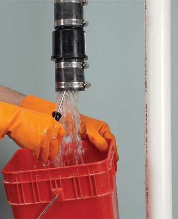 <b>Photo 1: Remove the old valve</b></br> Push a long screwdriver up into the old check valve to drain the water above the valve.
