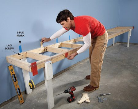 <b>Photo 1: Fasten base to wall</b></br> Support the base frame with temporary legs and screw it to wall studs. Use a string line and shims to make sure the front edge is perfectly straight.