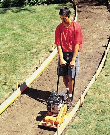 <b>Pack the base</b></br> A plate compactor is a heavy vibrating machine that solidly packs a soil or gravel base.