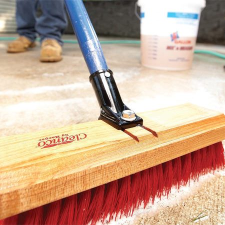 <b>Photo 2: Clean and rinse</b></br> Scrub the concrete using a stiff broom to clean dirt off the surface. Then rinse the entire patio with water.