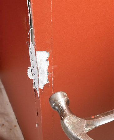 <b>Photo 1: Reshape bent metal corner bead</b></br> Shape the corner bead with a hammer until it's flush with the walls. Don't worry about making drywall cracks along the corner worse.