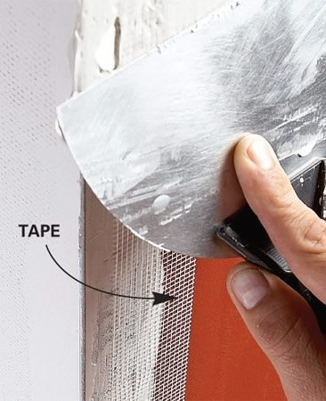 <b>Photo 2: Apply tape and compound</b></br> Cover the crack with mesh tape, then cover the tape and the corner bead with joint compound. Fill in one side, let it dry, then fill in the other side.