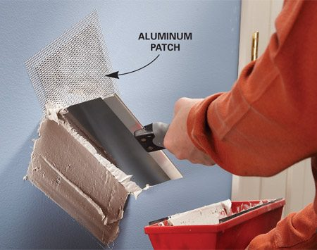 <b>Set the patch and apply compound</b></br> Cut the aluminum patch oversize, apply it and cover it with at least two coats of drywall compound.