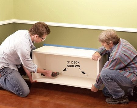 <b>Photo 8: Fasten with screws</b></br> Align the box with the outline and screw it to the wall studs with 3-in. deck screws.