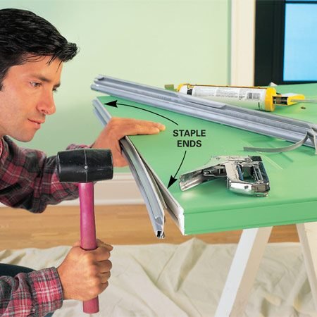 <b>Photo 4: Attach new sweep</b></br> Peel out the old door sweep and caulk the ends of the door frame. Tap in the replacement sweep and staple the ends with 1/2-in. staples or the fasteners provided with the sweep.