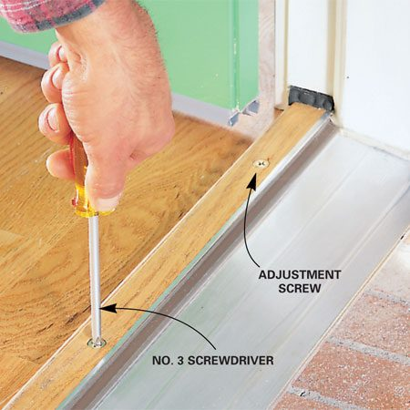 <b>Photo 5: Adjust threshold</b></br> Adjust the door threshold with a No. 3 Phillips screwdriver. Move it up or down until the door closes smoothly with no light seeping through.