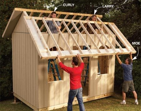 <b>Photo 6: Lift the roof into place</b></br> Gather some helpers to help lift the roof sections into place. Don't forget to toenail every rafter to the wall before you start the roof sheathing.