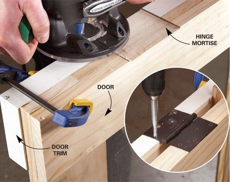 <b>Photo 10: Route the door hinges</b></br> Eliminate measuring mistakes by clamping the door and trim together before routing for the hinges. Make sure the trim piece extends 1/8 in. above the top of the door before you clamp it.
