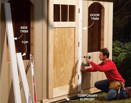 <b>Photo 11: Attach the door trim</b></br> Center the door on the opening and screw through the trim to attach it. Support the door with a temporary 2x4 screwed to the platform. Attach the opposite side trim and finally the top.
