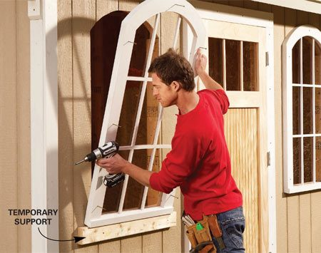 <b>Photo 15: Install the windows</b></br> Rest the window on the temporary 2x4 and screw it to the wall. Center the window on the opening before driving the screws.