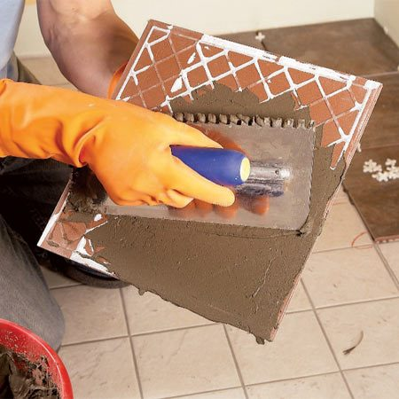 <b>Photo 2: Spread adhesive</b></br> Spread a flat layer of thin-set on the back of large tiles for better adhesion. Or, use a larger-notch trowel.