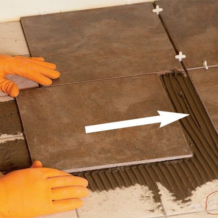 <b>Photo 3: Set the tile</b></br> Press the tile onto the floor thin-set and slide it perpendicular to the combed lines.