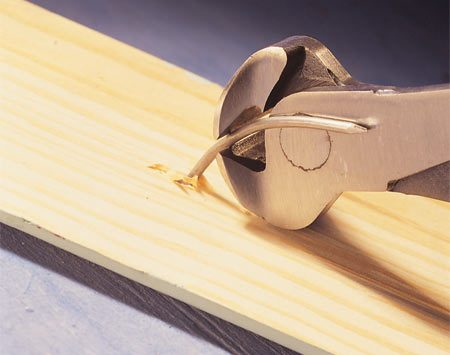 <b>Photo 2: Pull nails from the backside</b></br> Grab the nail shaft near the wood with a pair of nippers. Roll the tool head against the wood to pull the nail out the back side of the trim.