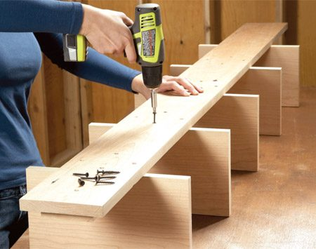 <b>Photo 2: Strengthen the shelves</b></br> Strengthen the shelves by driving screws through the backboard into the shelves and spacers. Drill screw holes with a countersink bit.