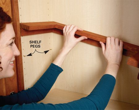 <b>Photo 2: Install the shelf</b></br> Set the spice shelf on adjustable shelf pegs. You may have to remove an existing shelf so you can tilt the spice shelf into place.