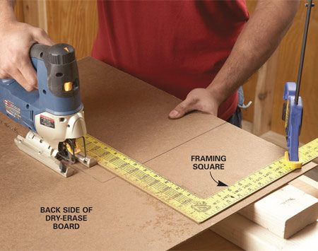 <b>Photo 1: Cut the board</b></br> Cut the dry-erase board from the back to avoid chipping the plastic-coated face. Use a framing square as a guide to get a straight cut.
