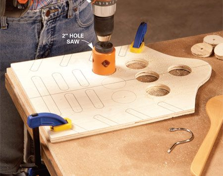 <b>Photo 1: Drill holes</b></br> Drill scarf holes with a 2-in. hole saw. Clamp the plywood tightly against a piece of scrap wood to prevent chipping as the hole saw exits the plywood.