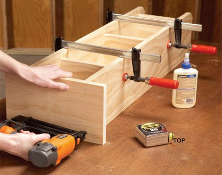 <b>Photo 2: Assemble the cabinet</b></br> Glue and nail the back and shelves between the sides, then add the top. After painting or staining, screw on hooks for the ironing board.