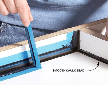 <b>Photo 2: Tape and caulk corners</b></br> Caulk the corners of the form. Any imperfections in the caulk will show up on the tabletop. So use masking tape to create neat, even edges.