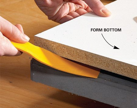 <b>Photo 6: Pull the form</b></br> Remove the form, starting with the sides. Then flip the tabletop over and pry off the bottom panel with a plastic putty knife.