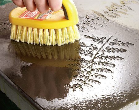 <b>Photo 7: Clean the top</b></br> Scrub the leaves out of their imprints with a stiff plastic brush. Scour the whole surface to remove excess colorant and Melamine residue.