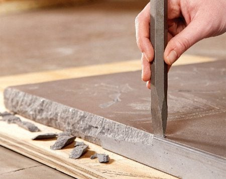 <b>Photo 8: Texture the edges</b></br> Create a natural stone look by chipping the edges with a cold chisel. Chip around all four edges, then flip the top over and chip from the other side.