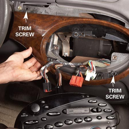 <b>Photo 1: Remove the radio</b></br> Pull the radio (if required) using a set of radio removal tools (available for a few dollars at any auto parts store). Then remove the bottommost trim panel screws and pop off the panel to reach the screws for the panel above.