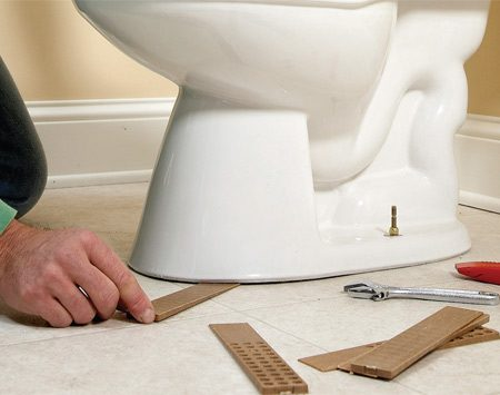 <b>Rot-proof shims</b></br> A toilet that rocks on an uneven floor will eventually break the wax ring seal and leak. So check for wobbles after you've set the toilet in place and loosely tightened the nuts. For slight wobbles, slip coins or stainless steel washers into the gaps under the toilet. Don't use regular steel washers, which might rust and stain the floor. For larger gaps, use shims. There are plastic shims made especially for toilets, but plastic construction shims like the ones shown here work just as well. When you've eliminated the wobble, tighten the nuts, cut off the shims and caulk around the toilet base. A toilet set on thick vinyl flooring can loosen as the vinyl compresses. In that case, just retighten the nuts a few days after installation.