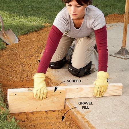 <b>Photo 2: Screed the gravel</b></br> Level the gravel about 3-1/2 in. below the top of the sidewalk to allow room for the bricks and about an inch of sand. A 2x4 with a scrap of plywood screwed to it makes a perfect notched screed board.
