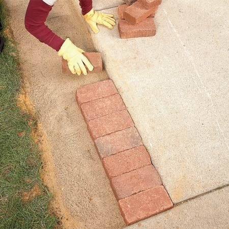 <b>Photo 5: Place the bricks</b></br> Set the bricks on the sand bed. Don't worry if the tops aren't even. You'll tamp them down later to level them out and make them flush to the sidewalk.