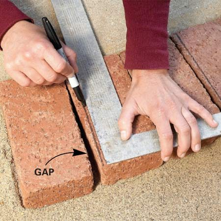 <b>Photo 6: Mark cuts for curves</b></br> Mark bricks to fit around a curve by simply setting them in place. Then estimate how much you'll have to cut off to close the gap between bricks and draw a cutting line with a permanent marker.