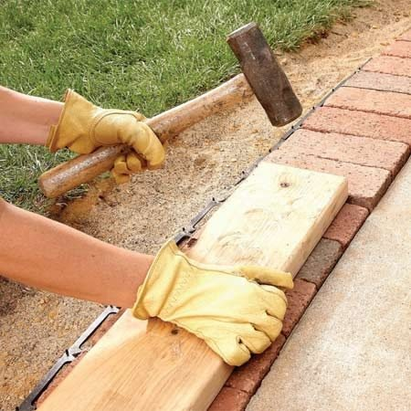 <b>Photo 9: Tamp the bricks</b></br> Level the tops of the paver bricks with a board and hand maul. Tamp them down flush to the surface of the sidewalk.