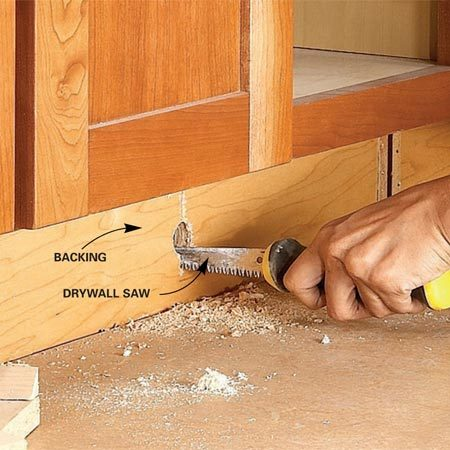 <b>Photo 1: Remove the toe kick</b></br> Break out the toe-kick backing to open up the spaces under the cabinets. Just drill a hole near the center, cut the backing in half and pull it out.