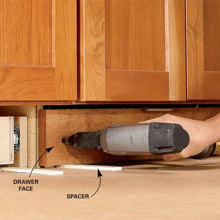 <b>Photo 6: Fasten the drawer face</b></br> Rest the drawer faces on 1/4-in. spacers. Tack the face in place with two nails, then open the drawer and drive screws into the face from the inside of the drawer box.