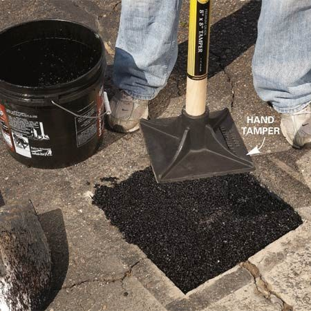 <b>Photo 5: Pack in new asphalt</b></br> Fill the cutout with new asphalt. Be sure to repack the gravel base first. Then add asphalt in 1-in. layers, packing each layer with a hand tamper.