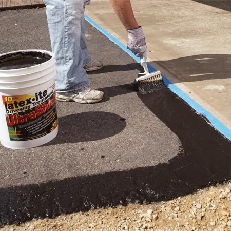 <b>Photo 8: Coat the perimeter</b></br> Apply the sealer around the perimeter of the driveway. Protect walls and the adjacent concrete with wide masking tape.
