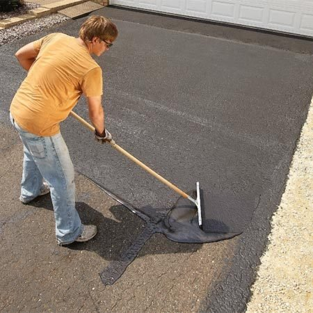 <b>Photo 9: Apply the sealer</b></br> Spread the sealer by working back and forth across the driveway. Pull the broom or squeegee at an angle to plow the excess sealer onto the uncoated area.