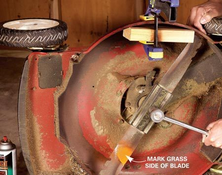 <b>Photo 2: Remove the blade</b></br> Clamp a block to  the lawn mower   skirt to stop  the blade from spinning   while you  unscrew the nut. Use the longest   wrench you can  find to loosen the nut. It's   likely to be very tight.