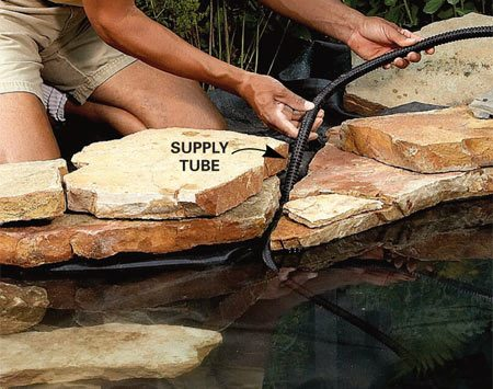 <b>Photo 4: Lay the stone</b><br/>Surround the pond with stones. Leave a gap between stones so you can remove the waterfall supply tube if necessary. Do the same for the pump&#39;s power cord.