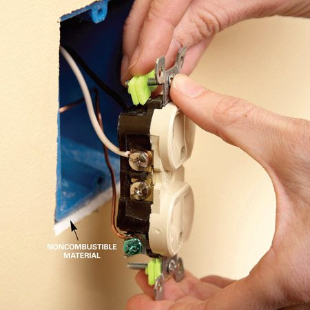 <b>Photo 1: Remove the screws </b></br> Turn off the power and check with a voltage tester to make sure there's no power to the outlet. Unscrew the outlet and add enough shims to bring the outlet flush to the wall.