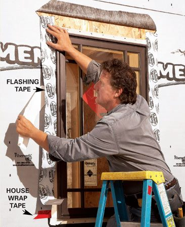 <b>Photo 6: Flashing tape goes over flanges</b></br> Apply flashing tape over the nailing flanges of the window sides, draping it over the sill pan and behind the house wrap at the top. Apply more flashing tape at the top.
