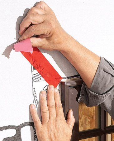 <b>Photo 7: Tape cuts in house wrap</b></br> Fold down and trim the house wrap at the top and seal all the seams with house wrap tape.