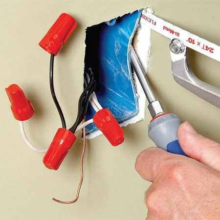<b>Photo 1: Cut the old box loose</b></br> To remove the old box, pry it away from the stud slightly to expose the nail shafts and cut them with a hacksaw. Then work the wires through the box as you pull it free of the hole.