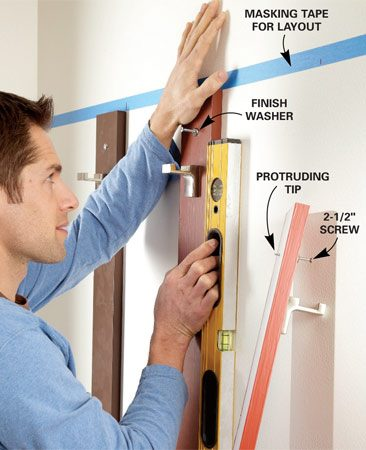 <b>Photo 1: Position the racks</b></br> Drive your screws partway into each board so the screw tips poke out the back. Place the boards where you want them, and press hard to mark the spots for your drywall anchors.