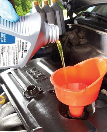 <b>Photo 3: Add fresh oil</b></br> Refill the engine using a funnel and recap the bottle (to prevent spills) before you toss it into the recycling bin.