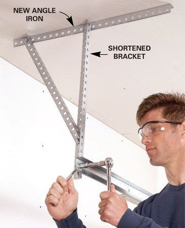 <b>Shorten the garage door bracket</b></br> Reattach the garage door tracks securely with metal angle iron. Buy a short length for the ceiling. Then cut the sides to position the track in its original location.